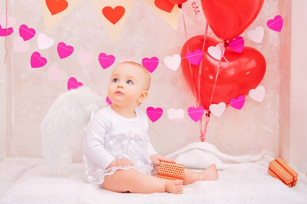 Porträt eines überraschten babys mit weißen federflügeln, mit geschenken in kisten, symbolen des valentinstags.