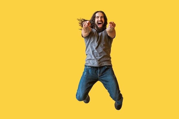 Porträt eines überraschten bärtigen jungen mannes mit langen lockigen haaren in grauem t-shirt, das springt, zeigt und die kamera mit erstauntem, fröhlichem, lustigem gesicht anschaut. indoor-studioaufnahme auf gelbem hintergrund isoliert.