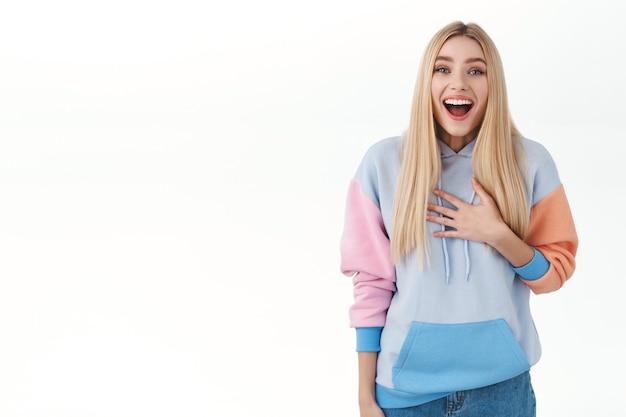 Porträt eines überraschten blonden mädchens im hoodie-look beeindruckt und fasziniert, brust berühren und den mund amüsiert öffnen