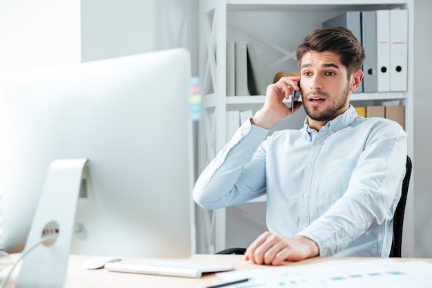 Porträt eines überraschten geschäftsmannes, der am arbeitsplatz im büro telefoniert