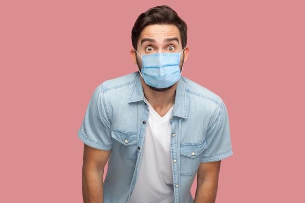 Porträt eines überraschten jungen mannes mit chirurgischer medizinischer maske im blauen hemd, der mit schockiertem, unglaublichem gesicht in die kamera schaut. indoor-studioaufnahme, isoliert auf rosa hintergrund.