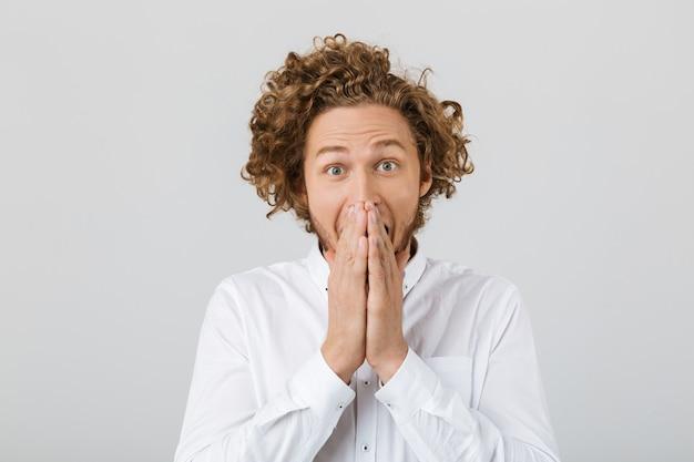 Porträt eines überraschten jungen mannes mit lockigem haar