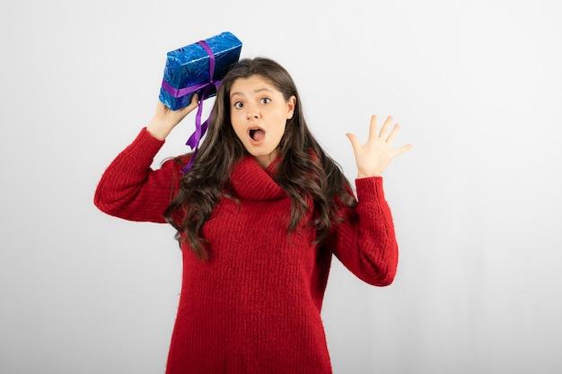 Porträt eines überraschten mädchens, das sich eine geschenkbox auf den kopf setzt.