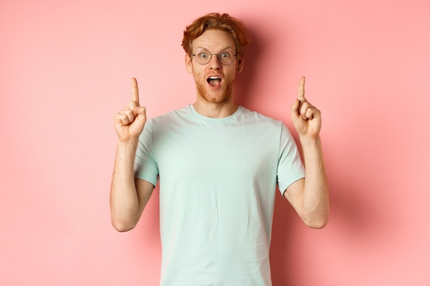 Porträt eines überraschten mannes, der die werbung auscheckt, die erstaunt nach luft schnappt und mit den fingern nach oben zeigt ...