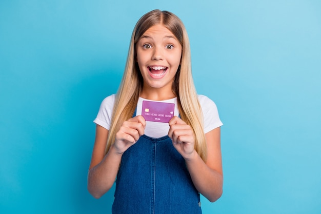 Porträt eines überraschten netten blonden mädchens mit langen haaren, das eine lässige kleidung mit kreditkarte zeigt, die auf pastellblauem hintergrund isoliert ist