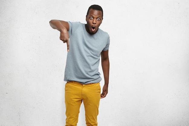 Porträt eines überraschten und schockierten stilvollen jungen schwarzen kunden, der erstaunt zeigefinger nach unten zeigt und preisverfall zeigt.