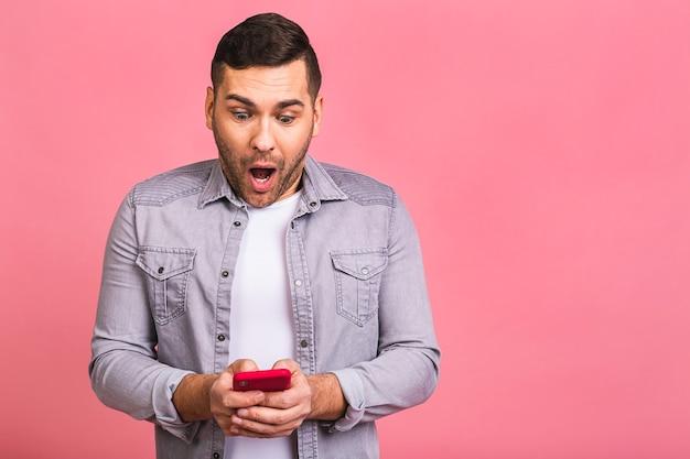 Porträt eines überraschten verblüfften schockierten lässigen jungen mannes, der handy ansieht. mit dem telefon eine sms senden.