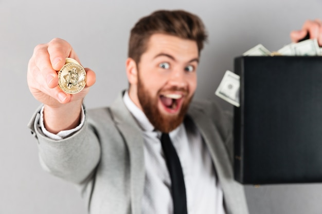 Porträt eines überzeugten geschäftsmannes, der goldenes bitcoin zeigt