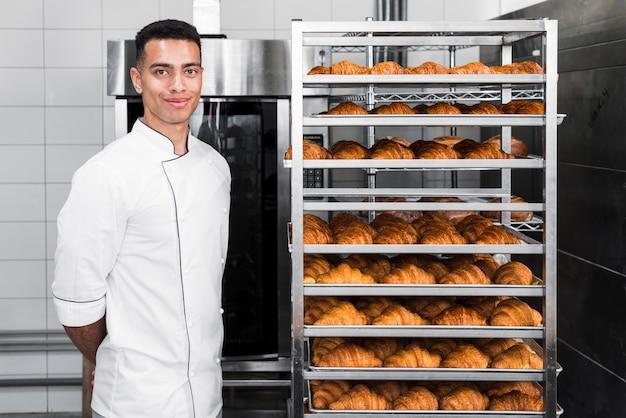 Porträt eines überzeugten jungen männlichen bäckers, der nahe den gebackenen hörnchenregalen steht