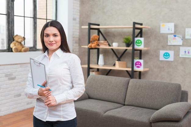 Porträt eines überzeugten lächelnden jungen weiblichen psychologen, der in der hand die kamera hält klemmbrett und bleistift betrachtet