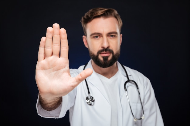 Porträt eines überzeugten männlichen doktors kleidete in der uniform an
