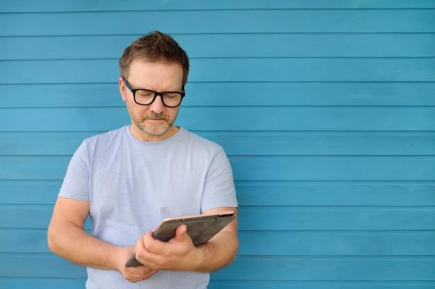 Porträt eines überzeugten reifen mannes, der tablet-computer hält