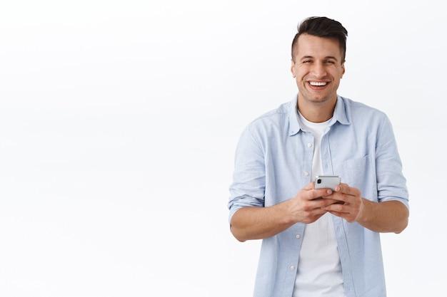 Porträt eines unbeschwerten, gutaussehenden kaukasiers, der über lustige meme oder blog-posts lacht, handy hält, freunden in selbstquarantäne sms schreibt, covid19-sperre, online in kontakt bleiben