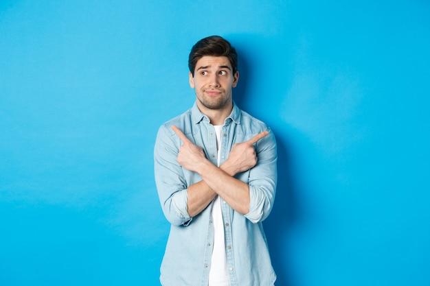 Porträt eines unentschlossenen erwachsenen mannes, der mit den fingern seitlich zeigt, aber nach links schaut und die wahl zwischen zwei produkten trifft und vor blauem hintergrund steht.