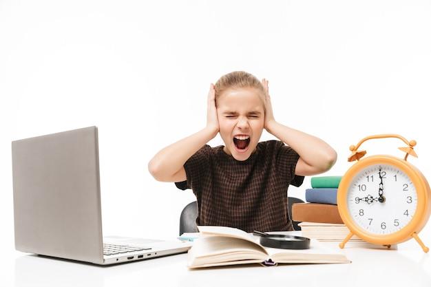 Porträt eines unglücklichen schulmädchens mit silbernem laptop beim lernen und lesen von büchern in der klasse isoliert über weißer wand
