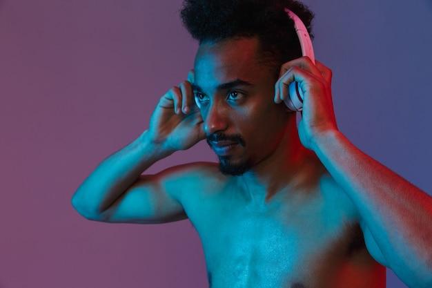 Porträt eines unrasierten, hemdlosen afroamerikaners, der mit kopfhörern über der violetten wand isoliert posiert