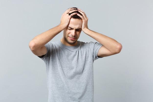 Porträt eines unzufriedenen jungen mannes in freizeitkleidung, der die augen geschlossen hält und die hände auf den kopf legt