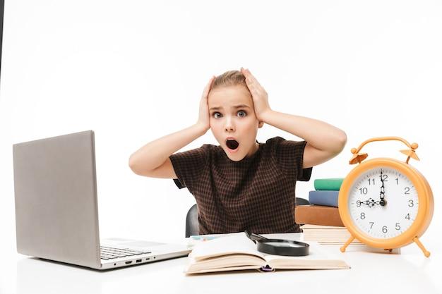 Porträt eines unzufriedenen schulmädchens mit silbernem laptop beim lernen und lesen von büchern in der klasse isoliert über weißer wand