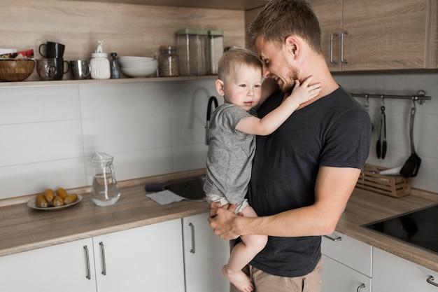 Porträt eines vaters, der seinen netten sohn steht in der küche trägt