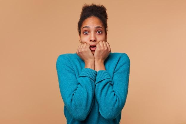 Porträt eines verängstigten jungen afroamerikaners, der einen blauen pullover mit lockigem dunklem haar trägt. mit weit geöffneten augen und mund, isoliert.