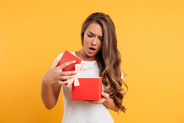 Porträt eines verärgerten enttäuschten mädchens, das geschenkbox öffnet