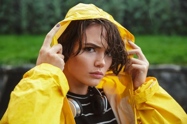 Porträt eines verärgerten jungen mädchens, das regenmantel trägt