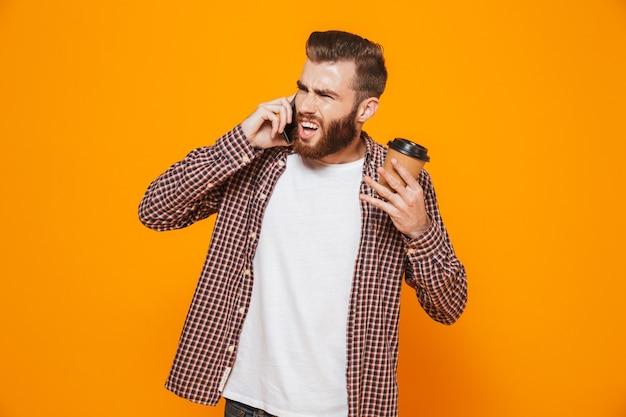 Porträt eines verärgerten jungen mannes, der freizeitkleidung trägt, die auf handy spricht, das kaffee zum mitnehmen trinkt