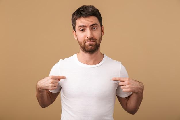 Porträt eines verärgerten jungen mannes, der lässig gekleidet steht und isoliert über beige steht und mit den fingern auf sein leeres t-shirt zeigt