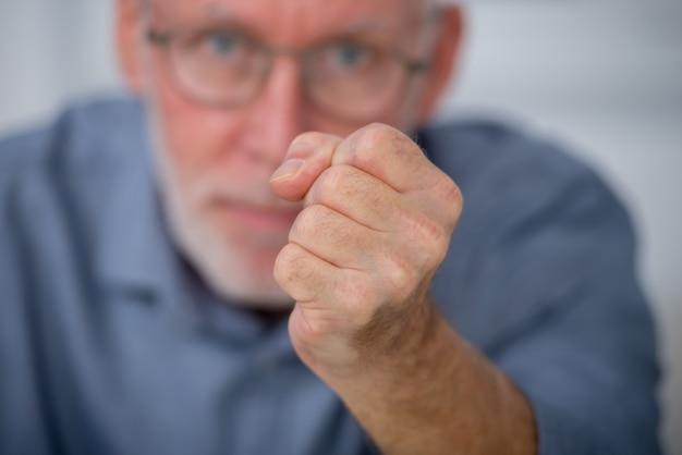 Porträt eines verärgerten mannes, nahaufnahme seiner faust