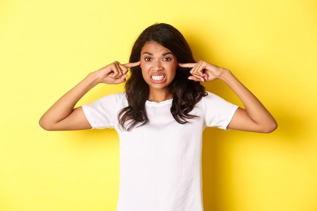 Porträt eines verärgerten und wütenden mädchens in weißem t-shirt, das sich über lautes geräusch beschwert, die ohren schließt und wütend aussieht und auf gelbem hintergrund steht.