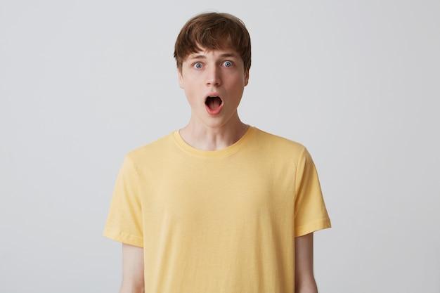 Porträt eines verblüfften hübschen jungen mannes mit kurzem haarschnitt