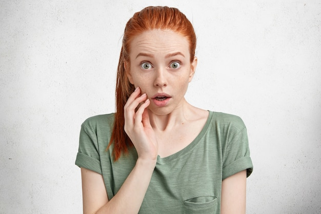 Porträt eines verblüfften rothaarigen weiblichen models mit überraschtem ausdruck, starrt mit verängstigtem blick, als sie merkt, dass sie vergessen hat, rechnungen zu bezahlen, afraids von etwas
