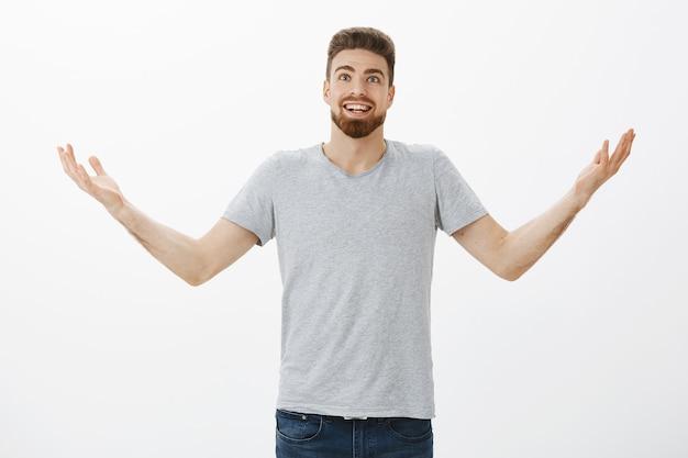 Porträt eines verblüfften und aufgeregten überraschten europäischen mannes mit bart und erhobenen händen in der luft, der freudig und dankbar aussieht und gott dafür dankt, dass er ihm geholfen hat, wünsche und träume über einer grauen wand zu erfüllen