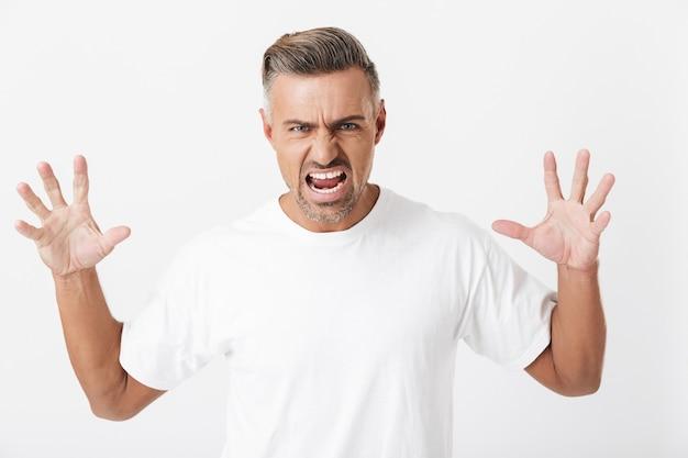 Porträt eines verklemmten mannes der 30er jahre mit borsten, der ein lässiges t-shirt trägt, das die hände hebt und isoliert auf weiß schreit