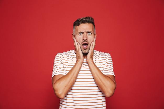 Porträt eines verklemmten nervösen mannes, der sein gesicht in verwirrung und stress packt, isoliert auf rot