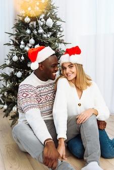 Porträt eines verliebten paares in sankt-hüten, die am baum sitzen. blendung der gelben girlande. schwarzer mann umarmt eine kaukasische frau
