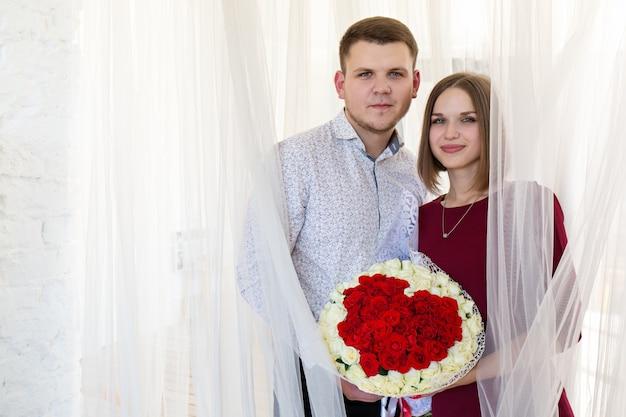 Porträt eines verliebten paares mit einem großen rosenstrauß