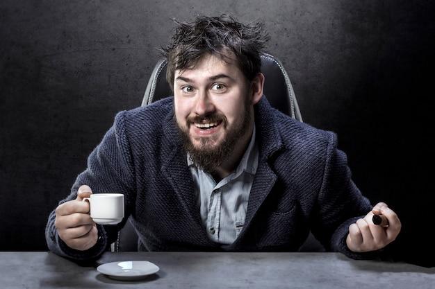 Porträt eines verrückten bärtigen mannes auf dem regiestuhl mit einer zigarre und kaffee in der hand