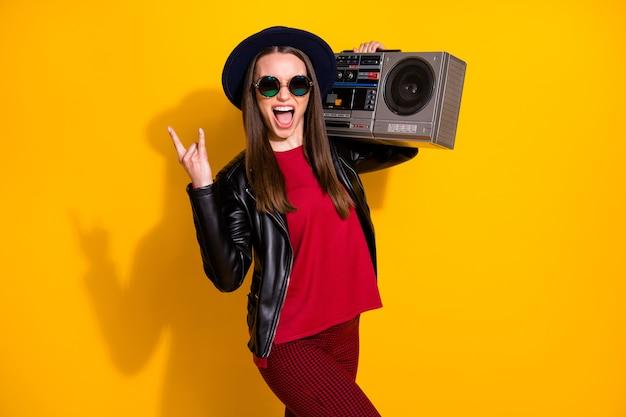 Porträt eines verrückten modischen mädchens, das boombox mit hornzeichen trägt