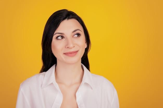 Porträt eines verträumten inspirierten mädchens suchen leeren raum auf gelbem hintergrund nach