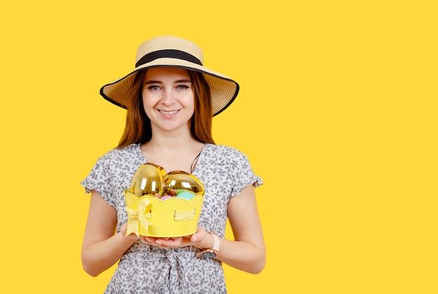 Porträt eines verträumten niedlichen mädchens präsentiert geschenke für die osterferien. kaukasisches junges mädchen, das eier hält.