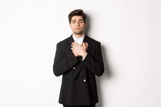 Porträt eines verträumten und herzlichen bärtigen mannes im anzug, augen schließen und die hände am herzen halten, sich an etwas erinnern, nostalgisch auf weißem hintergrund stehen