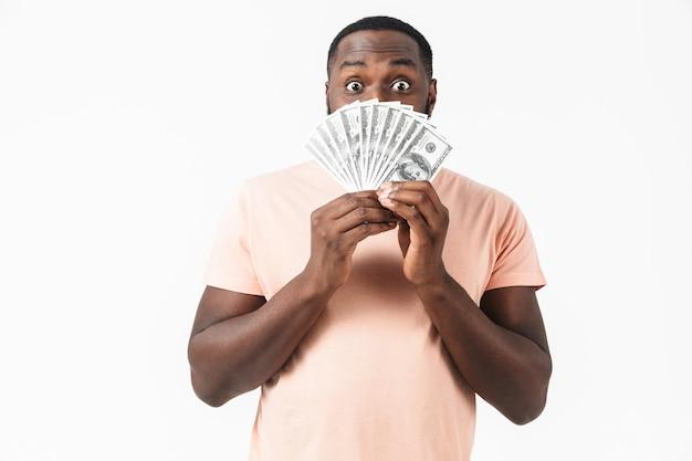 Porträt eines verwirrten afrikanischen mannes, der ein hemd trägt, das isoliert steht und geldbanknoten zeigt
