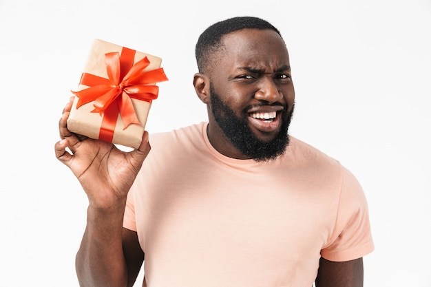 Porträt eines verwirrten aufgeregten afrikanischen mannes, der ein hemd trägt, das isoliert steht und eine geschenkbox zeigt