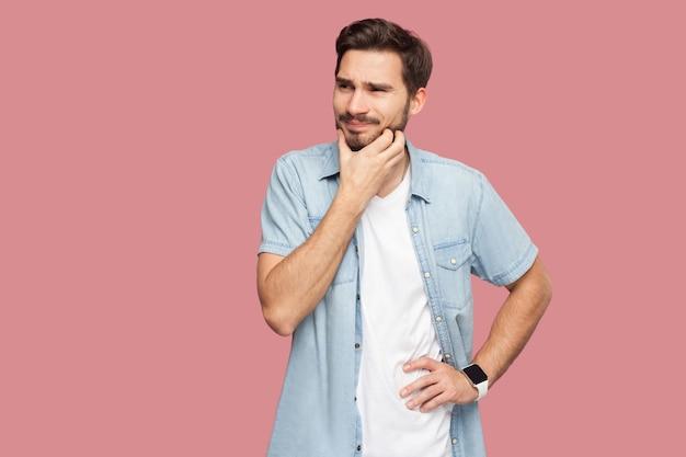 Porträt eines verwirrten, gutaussehenden, bärtigen jungen mannes im blauen hemd im casual-stil, der den bart kratzt und denkt, was er tun oder versuchen soll, eine antwort zu finden. indoor-studioaufnahme, isoliert auf rosa hintergrund.