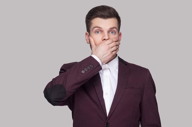 Porträt eines verwirrten, gutaussehenden jungen mannes in violettem anzug und weißem hemd, stehend, mit großen augen in die kamera blicken, die arme anheben und seinen mund blockieren. indoor-studioaufnahme, auf grauem hintergrund isoliert.