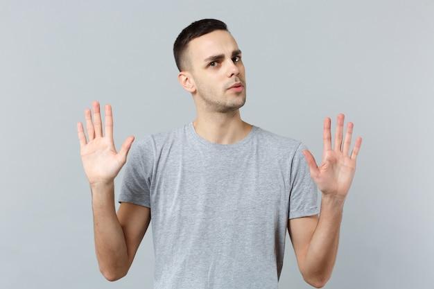 Porträt eines verwirrten jungen mannes in freizeitkleidung, aufsteigende hände, die handflächen zeigen