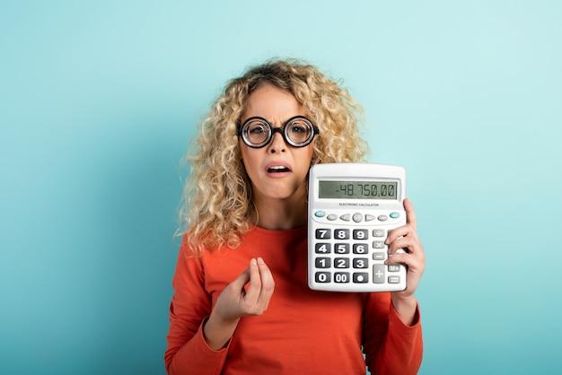 Porträt eines verwirrten mädchens, das eine brille trägt und einen taschenrechner hält