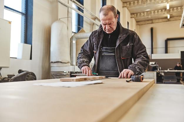 Porträt eines vielbeschäftigten handwerkers, der an seinem arbeitsplatz arbeitet