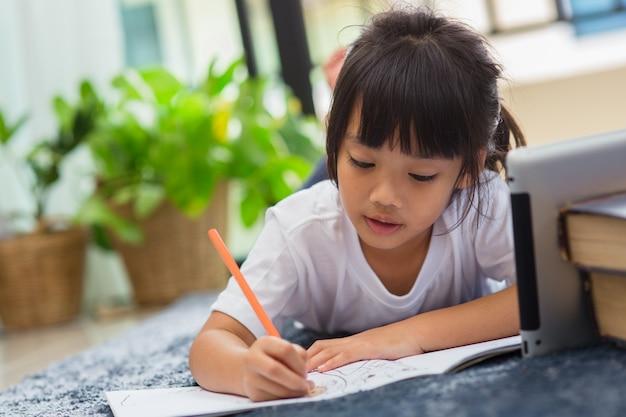 Porträt eines vorschulkindes, das tablet für seine hausaufgaben verwendet, weicher fokus des kindes, das hausaufgaben macht, indem es digitale tablets verwendet, um informationen über das internet, e-learning oder das bildungskonzept zu hause zu suchen